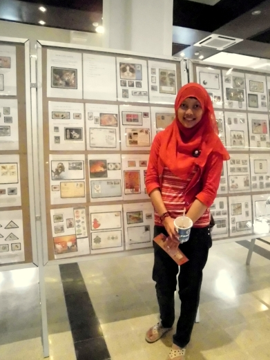 Emyl in front of postcards and stamps collection